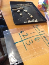 Two-digit addition and subtraction with pebbles (ones) and twigs (tens) - great way to bring natural resources into math as manipulatives!